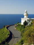 San Sebastian Bay Clifftop Lighthouse with Cyclist Riding Uphill Photographic Print by Christian Kober