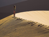 Young Woman Walks across the Dunes at Sunset at Sossusvlei, Namibia Photographic Print by Julian Love