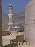 Blue and Gold Dome and Minaret of Masjid Sultan Qaboos are Framed by the Towers of Nizwa Fort Photographic Print by John Warburton-lee