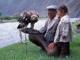 Mongolia, Kasakh Hunter with Eagle by the Khovd River, with a Small Child Fotografie-Druck von Antonia Tozer