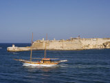 Valletta, A Fishing Boat Motors Out of the Entrance to the Grand Harbour Past Ricasoli Point, Malta Stampa fotografica di John Warburton-lee