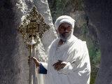 Old Ethiopian Orthodox Priest Holds a Large Brass Coptic Cross at Rock-Hewn Church of Adadi Maryam Photographie par Nigel Pavitt