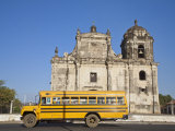Leon, American Yellow Bluebird Bus Driving Past San Juan Church, Nicaragua Photographie par Jane Sweeney