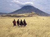 Maasai Warriors Stride across Golden Grass Plains at Foot of Ol Doinyo Lengai, 'Mountain of God' Photographie par Nigel Pavitt