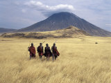 Maasai Warriors Stride across Golden Grass Plains at Foot of Ol Doinyo Lengai, 'Mountain of God' Fotografie-Druck von Nigel Pavitt