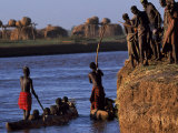 Dassanech Tribesmen and Women Load into a Dugout Canoe Ready to Pole across the Omo River, Ethiopia Photographic Print by John Warburton-lee