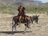 Two Happy Himba Girls Ride a Donkey to Market, Namibia Fotografie-Druck von Nigel Pavitt