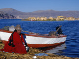 Indian Woman from the Uros or Floating Reed Islands of Lake Titicaca, Washes Her Pans in the Water  Fotografie-Druck von John Warburton-lee