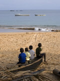 Four Small Boys Look Out to Sea from Where They Sit on Bamboo Fishing Boat on Island of Princip Photographic Print by Camilla Watson