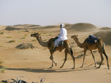 Bedu Rides His Camel Amongst the Sand Dunes in the Desert Photographic Print by John Warburton-lee