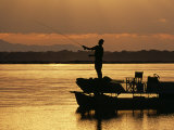 Lower Zambezi National Park, Fly Fishing for Tiger Fish from a Barge on the Zambezi River at Dawn,  Photographic Print by John Warburton-lee