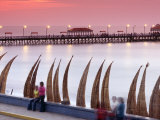 Waterfront Scene at Huanchaco in Peru, Locals Relax Next to Totora Boats Stacked Along the Beach Fotografie-Druck von Andrew Watson