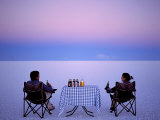 Tourists Enjoy Sundowners While Looking Out across the Endless Salt Crust of Salar De Uyuni Photographic Print by John Warburton-lee