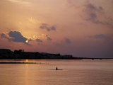 Fishermen Paddles His Small Boat across Tadjoura Bay at Sunrise Photographie par Nigel Pavitt