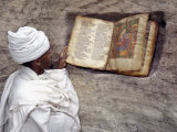 Priest of Ethiopian Orthodox Church Reads Old Bible at Rock-Hewn Church of Yohannes Maequddi Fotografisk tryk af Nigel Pavitt