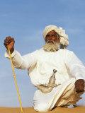 Bedouin Man Kneels on Top of a Sand Dune in the Desert Photographie par John Warburton-lee