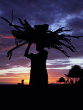 Dassanech Woman Carries a Bundle of Wood Home at Sunset, Omo Delta, Ethiopia Photographic Print by John Warburton-lee