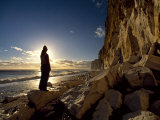 Silhouetted Figure Admires the Dramatic Coastal Landscape at Newhaven Photographic Print by Fergus Kennedy