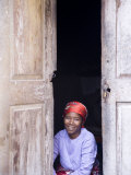 Woman Looks Out from Her Doorway on Ilha Do Mozambique Photographic Print by Julian Love