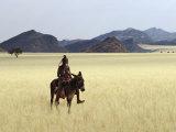 Old Himba Woman, Upright Despite Her Years, Rides Her Donkey Through Harsh Land Stampa fotografica di Nigel Pavitt