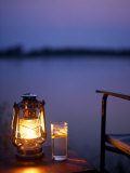 Gin and Tonic by the Light of Hurricane Lamp, Looking Out over the Zambezi River, Zambia Photographic Print by John Warburton-lee