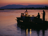 Lower Zambesi National Park, Guests Enjoying Sundowners on a Barge on the Zambezi River, Zambia Photographic Print by John Warburton-lee