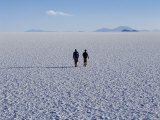 Two Tourists Walk across the Endless Salt Crust of Salar De Uyuni, the Largest Salt Flat in World Photographic Print by John Warburton-lee