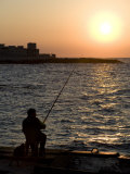 Fisherman Watches as the Sun Goes Down on the Waterfront of Alexandria, Egypt Photographic Print by Julian Love