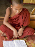 Burma, Lake Inle, A Young Novice Monk Learning at a Monastery School on Lake Inle, Myanmar Photographic Print by Nigel Pavitt