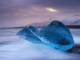 Translucent Blue Iceberg Washed Ashore on Breidamerkursandur Black Sands Photographic Print by Patrick Dieudonne