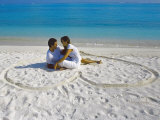 Young Couple on Beach Sitting in a Heart Shaped Imprint on the Sand, Maldives, Indian Ocean, Asia Photographic Print by Sakis Papadopoulos