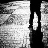 Silhouette of Mans Legs Walking on Cobblestone Street at Night Photographie par Elke Hesser