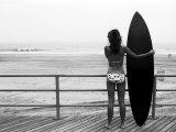 Malli musta surffilauta seisoo Boardwalk ja katsella aalto rannalla Valokuvavedos tekijänä Theodore Beowulf Sheehan