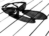 Black and White Image of Sunglasses and their Shadow on a Table Photographic Print by Claire Morgan