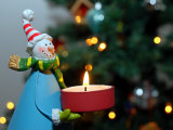Close-Up of a Snow Man Candle in Front of a Tree with Christmas Lights Photographic Print by Winfred Evers