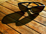Sunglasses and their Shadow on a Wooden Table Photographic Print by Claire Morgan