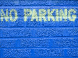 Painted Blue Brick Wall with No Parking Sign Photographic Print by John Nordell