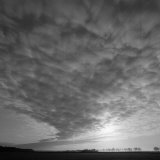 Clouds Obscure the Sun in a Huge Sky with Trees on the Horizon Photographic Print by Lynn Johnson