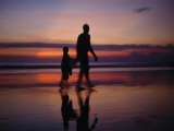 Man and Child Walk Along Kuta Beach at Sunset Photographic Print by  xPacifica