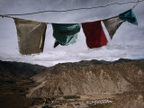 Prayer Flags and a Prison in the Valley Below Photographic Print by Lynn Johnson