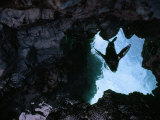 Looking Through a Hole in Volcanic Rock at Blue Water Above Photographic Print by Mattias Klum