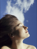 Young Woman Profiled Against a Cloud Filled Sky on a Sunny Day Photographic Print by Paul Damien
