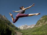 Agile Young Woman Jumping High in the Air in a Mountain Landscape Photographic Print by Pete McBride