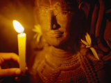 Man Holds a Candle Up to a Stone Carving at the Angkor Wat Temple Photographic Print by  xPacifica