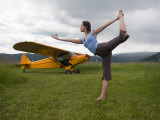 Young Woman Practicing Yoga by an Airplane Photographic Print by Pete McBride