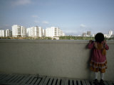 Little Girl Looks over a Wall Toward High Rises Near Hong Kong Fotografisk trykk av Lynn Johnson