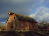 Rustic Barn Stands under a Cloud-Blanketed Sky Photographic Print by Joel Sartore