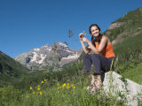 Young Woman Sitting on a Boulder in a Scenic Mountain Landscape Photographic Print by Pete McBride