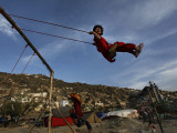 Afghan Girl Plays on a Swing Outside the Kart-E-Sakhi Shrine in Kabul, Afghanistan Photographic Print