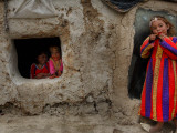 Displaced Girls Smile as They Look Out from a Shanty, in a Refugee Camp in Kabul, Afghanistan Photographic Print